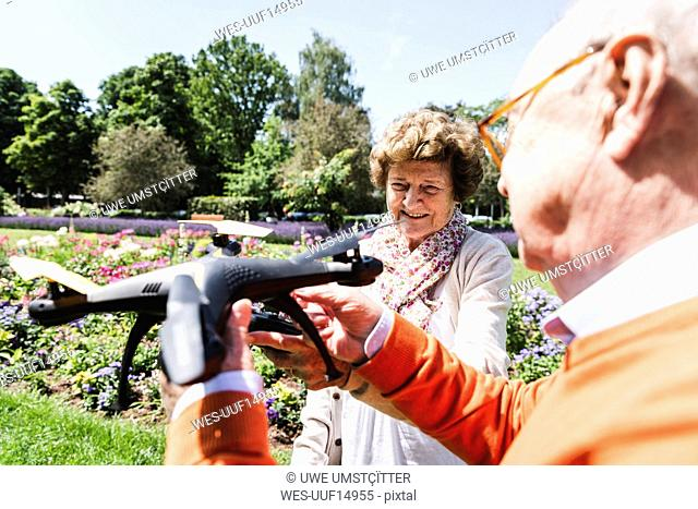 Senior couple playing with a drone in park