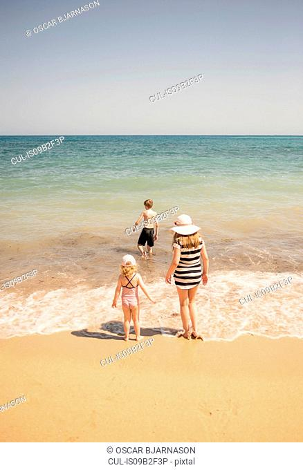 Rear view of woman with son and daughter paddling in sea, Altea, Alicante Province, Spain