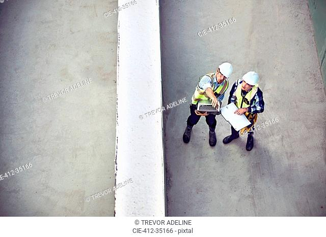 Construction worker and engineer with laptop talking at construction site