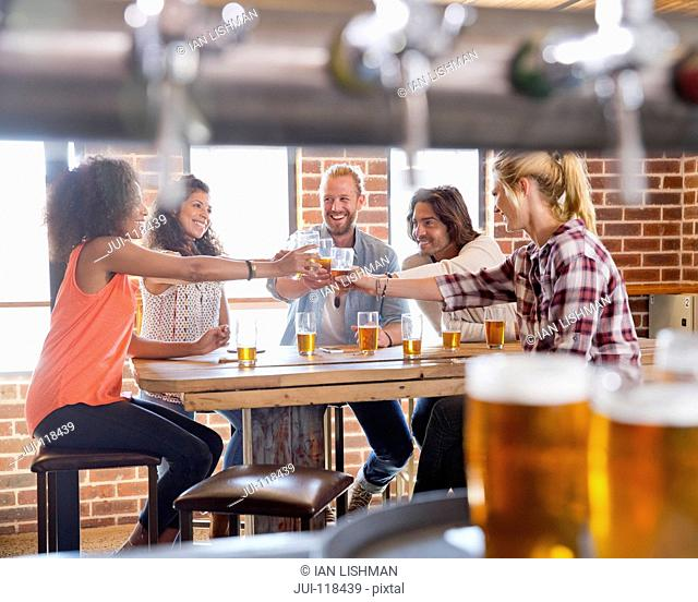 Group Of Young Friends Making Toast In Bar Together