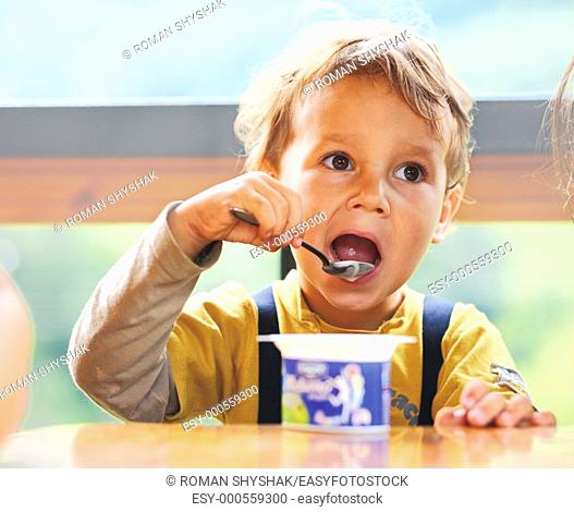 Little boy is eating yogurt, holding a spoon in his hand, sitting at the table