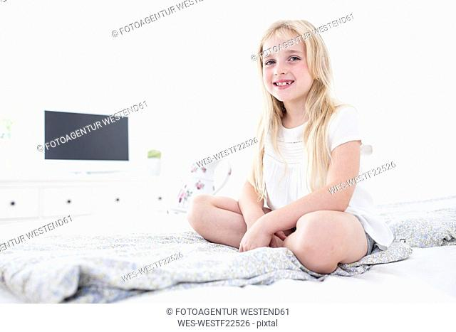 Portait of smiling girl sitting on bed