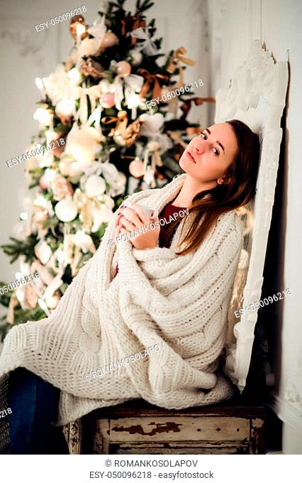 Young woman relaxing with a mug of coffee as she cuddles up in warm blanket on ancient commode. Her eyes closed and serene expression