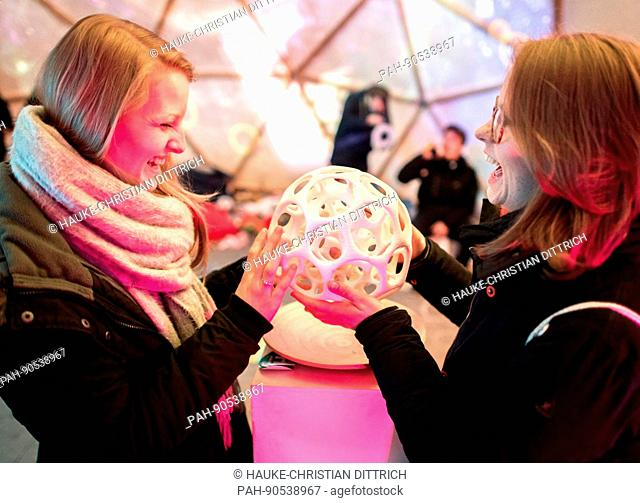 With a bluetooth ball Lina and Julia control an interactive photo presentation, which is projected into the dome of a tent