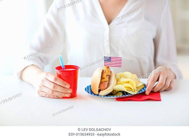 independence day, celebration, patriotism and holidays concept - close up of woman eating hot dog with american flag decoration and potato chips
