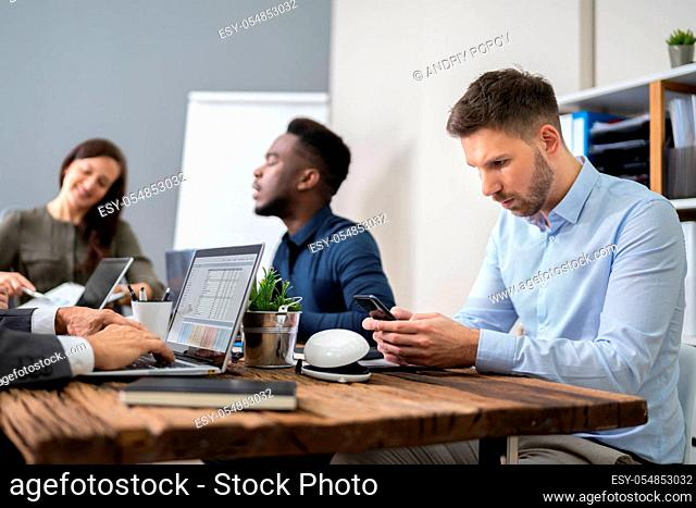 Distracted Businessman Using Mobile Phone In Meeting