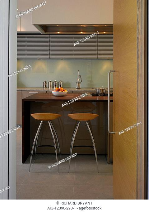 Pond and Park House, Dulwich, London. View through open pale wood modern door to kitchen with bar stools