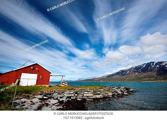 Cabin overlooking a fjord and snowy mountains in Lyngen Peninsula, Troms county, Norway, Europe
