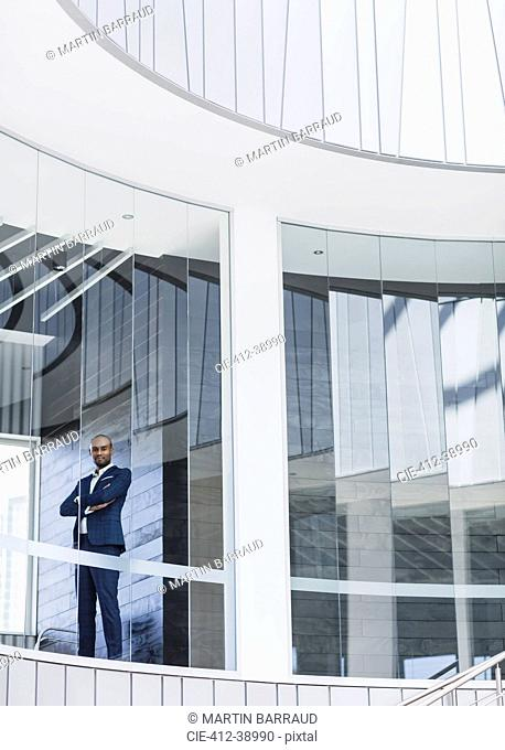 Portrait confident, serious CEO businessman standing at modern office window