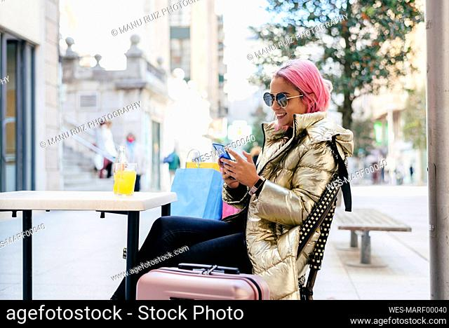Smiling pink hair woman using mobile phone while sitting at sidewalk cafe