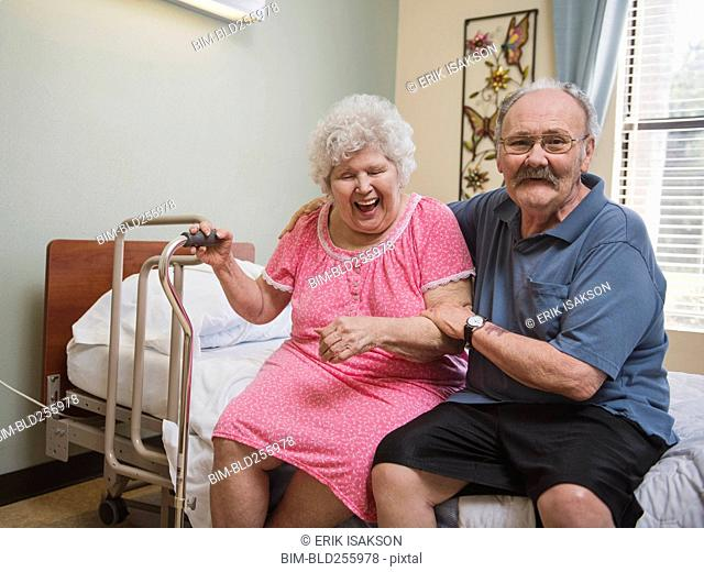 Caucasian man sitting on bed hugging laughing woman