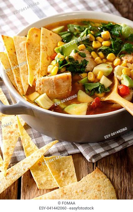 Homemade tortilla soup with chicken and vegetables close-up in a pot on the table. vertical