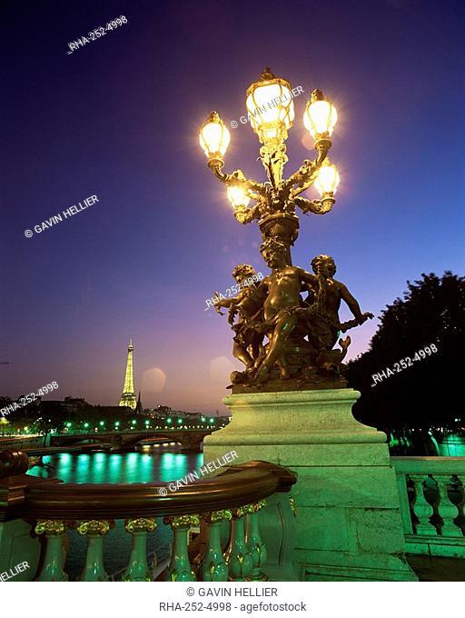 Eiffel Tower illuminated at dusk from Alexandre III Bridge, Paris, France, Europe