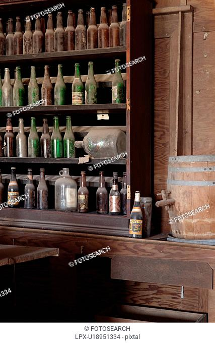 Drinking saloon as seen from inside with beer bottles behind bar, desaturated image, Bodie pioneer village, California