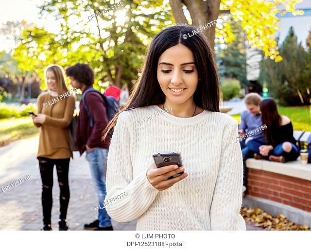 A young female university student of Lebanese ethnicity checks her smart phone while her friends are talking together in the background on the university...