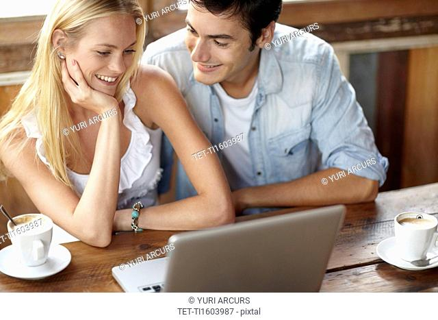 Couple using laptop in cafe