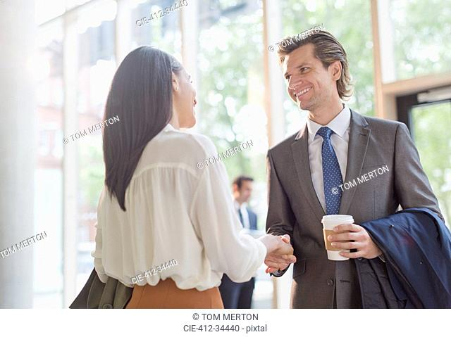Businessman with coffee and businesswoman handshaking in office lobby