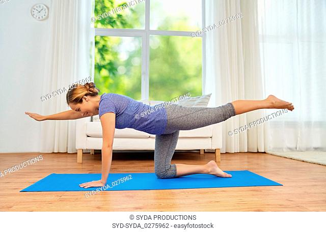 woman doing yoga cat pose at home