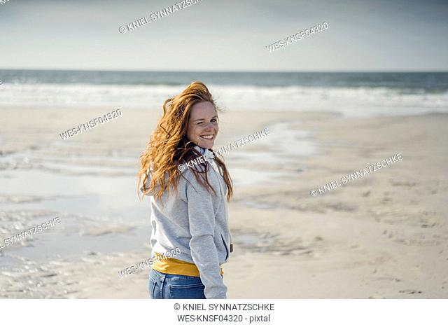 Redheaded woman relaxing on the beach, laughing
