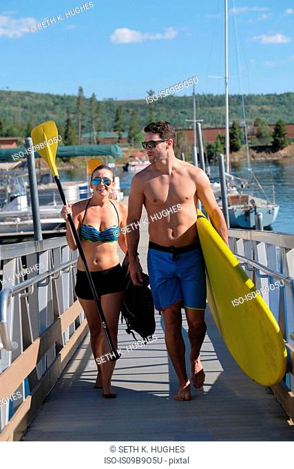 Paddleboarding couple carrying paddleboard on lake pier, Frisco, Colorado, USA