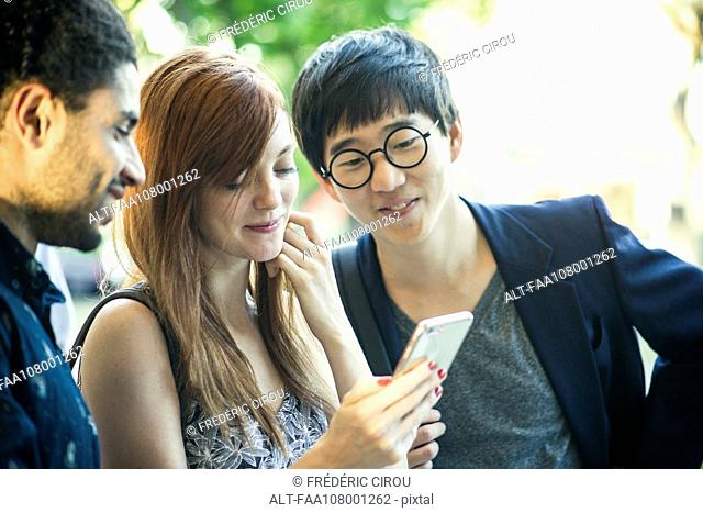 Young adult friends watching video on smartphone together