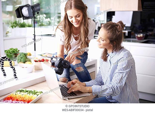 Two food bloggers choosing photos on digital camera