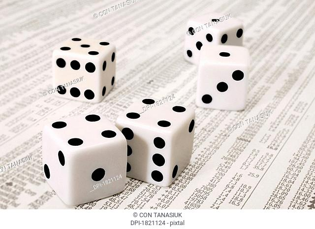 Dice on the stock market section of the newspaper