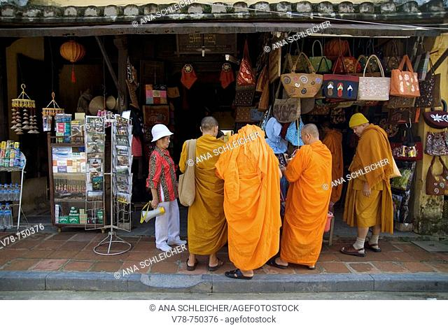 Group of male buddist monks, accompained by a tourist guide, shopping souvenirs in Hoi An, the best preserved town of Vietnam