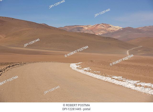 A road winds it's way through the high desert of Bolivia's Altiplano; Sur Lipez, Bolivia