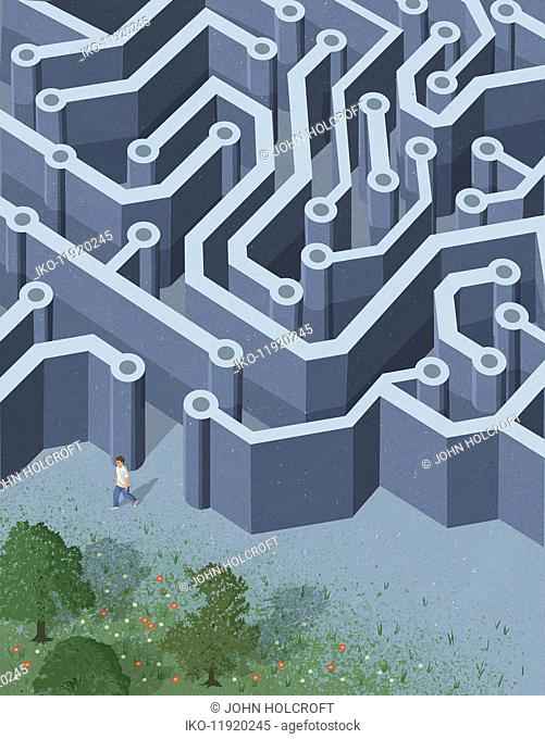 Teenager leaving grey circuit board maze for green outdoors