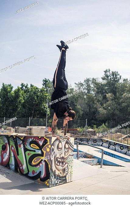 Tattooed man doing handstand in a skatepark