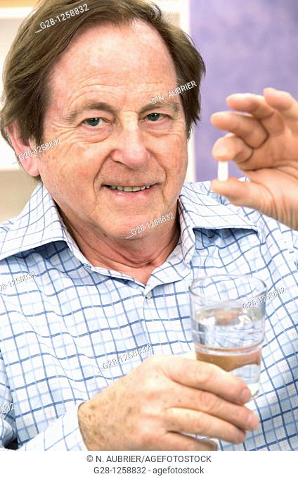 smiling senior man holding a tablet in one hand and a glass of water in the other hand about to take his medical treatment