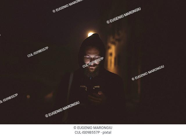 Man looking down at smartphone at night, Venice, Italy