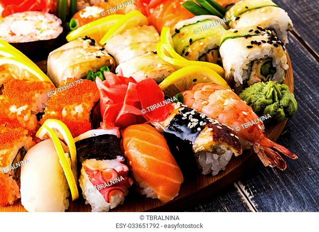 Sushi Set: sushi and sushi rolls on wooden plate, selective focus