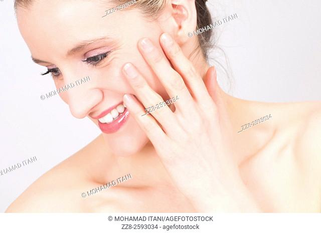 Happy young woman hand touching face