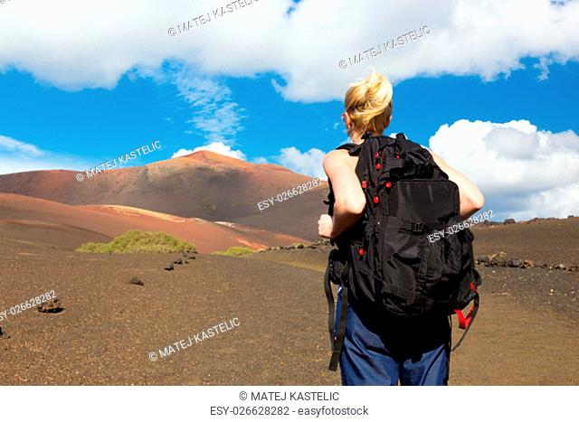 Woman hiking in nature can see the peak of Timanfaya volcano, nearly made it to top