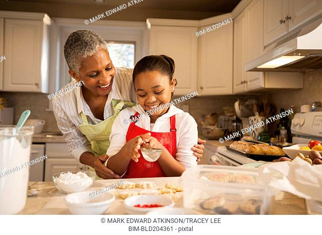 Woman and granddaughter baking in kitchen