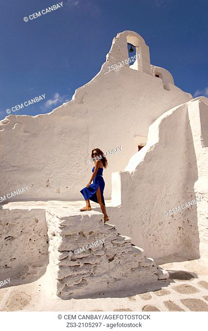 Woman posing on the steps of Paraportiani Church, Mykonos, Cyclades Islands, Greek Islands, Greece, Europe