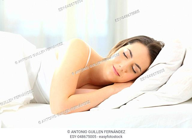 Relaxed woman sleeping on a bed at home in the morning with daylight
