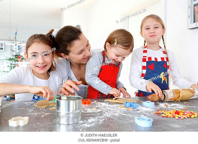 Girls with mother at kitchen counter making cookies smiling