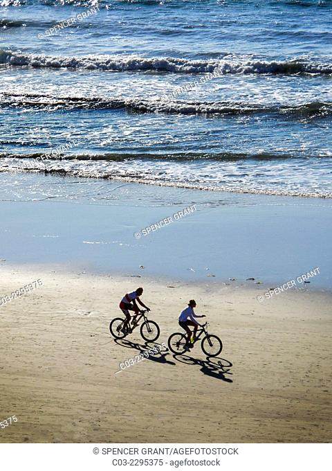 Throwing shadows in the afternoon sunlight, two bicyclists ride next to the Pacific Ocean surf in Laguna Beach, CA