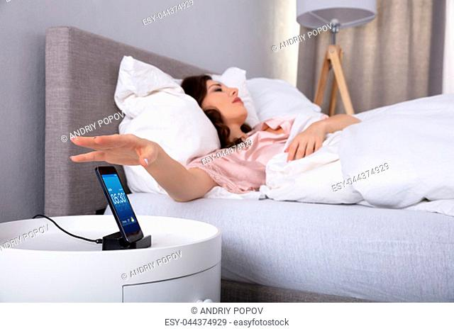 Sleeping Young Woman Lying On Bed Turning Off Alarm On Cellphone
