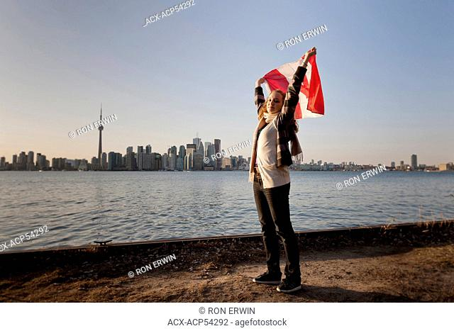 Young woman waving a Canadian flag at the water's edge on Algonquin Island, one of the Toronto Islands, the skyline of downtown Toronto