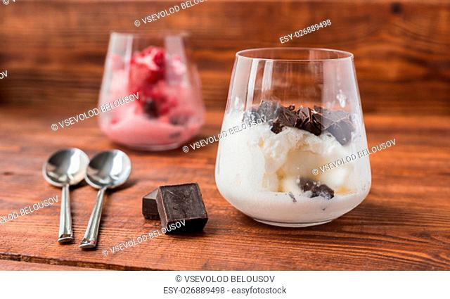 Two portions of vanilla and strawberry ice cream in glass on wooden table