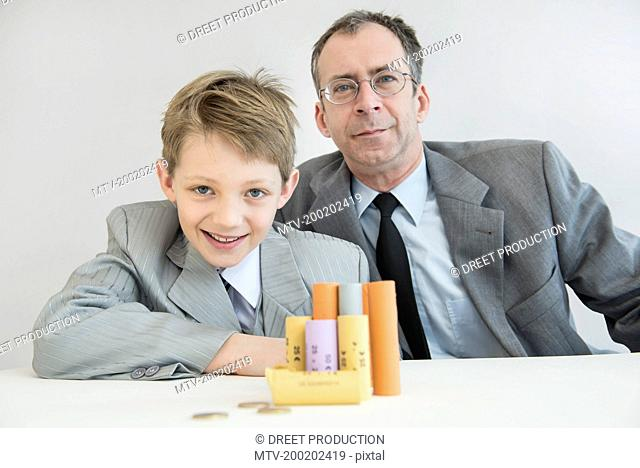 Father and son with Euro coin and coin rolls, smiling, portrait
