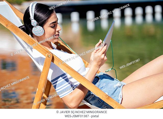 Young woman sitting in a deckchair wearing headphones and using tablet