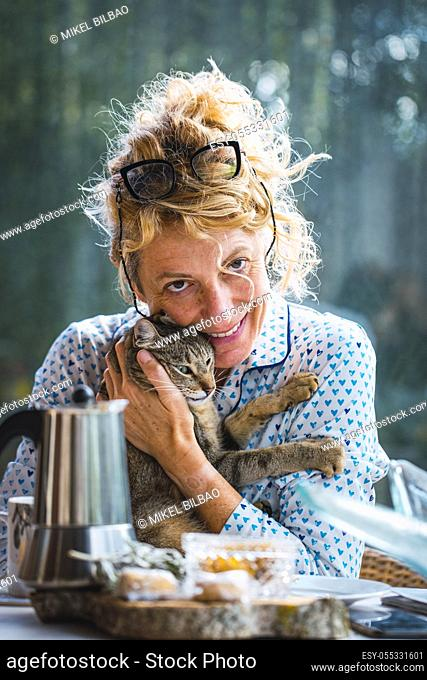 Blonde young mature woman with glasses in pyjamas at home in breakfast time, reading a magazine and having a moment with his cat
