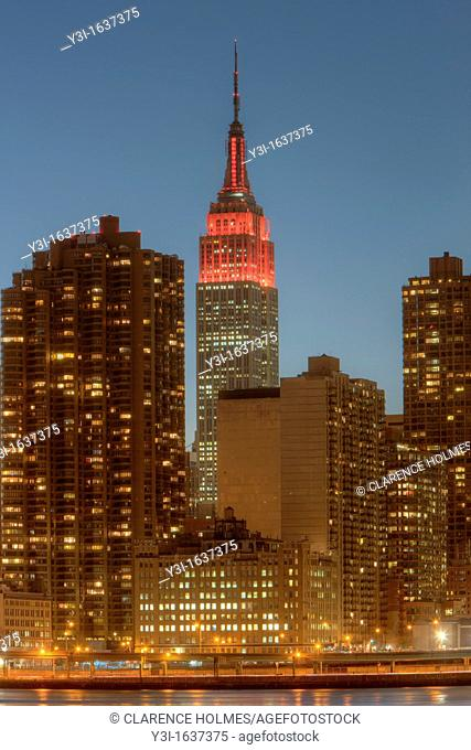 The Empire State Building and other Manhattan buildings at twilight in New York City, USA. The Empire State Building was lighted in red in honor of World Aids...