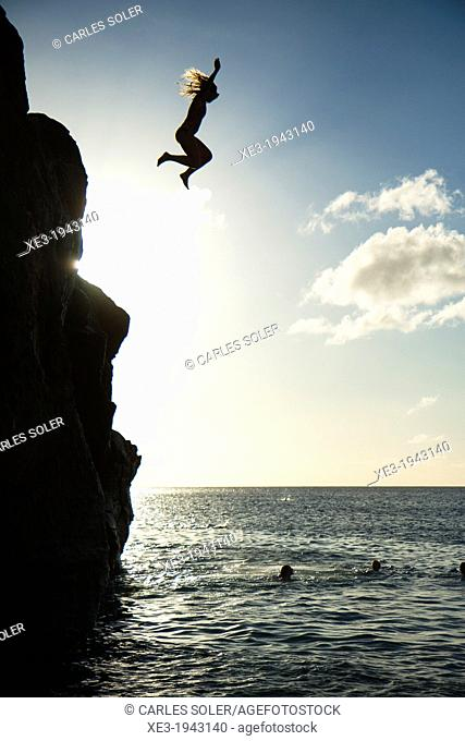 Girl jumping into water, Waimea Bay, Oahu, Hawaii