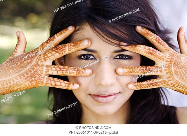 Portrait of a young woman showing her henna tattooed hands